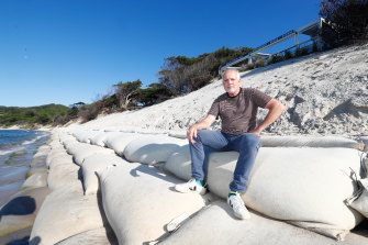 Beach Byron Bay restaurant owner Ben Kirkwood sits on a sandbag placed to save his business at Clarkes Beach.