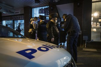 Police take the details of people outside the synagogue on Tuesday.