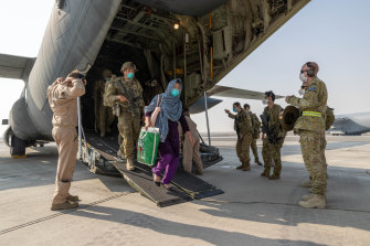 Afghanistan evacuees and Australian soldiers disembark a Royal Australian Air Force C-130J Hercules aircraft at Australia's main operating base in the Middle East, after their flight from Kabul.