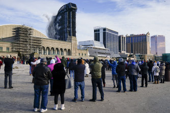 People gather to watch as the former Trump Plaza casino is demolished in a controlled explosion.