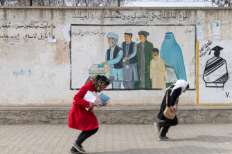 Girls head home from school in Kabul past a mural promoting voting for men and women.