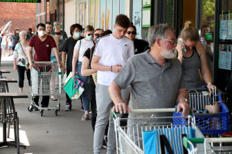 Shoppers queue at an Adelaide Woolworths after the announcement on Wednesday.