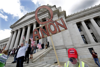 A demonstrator holds a QAnon sign as he walks at a protest opposing Washington state's stay-home order.