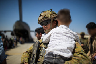 An Australian Army soldier carries an Afghan child while assisting a family aboard the RAAF C-17A Globemaster at the Hamid Karzai International Airport.