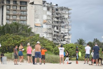 People on the beach look at the destruction to the oceanfront apartment complex.