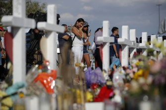 People visit a makeshift memorial at the site of a mass shooting at a shopping complex, in El Paso in August.