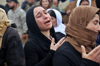 Iraqi Yazidi women mourn during the exhumation of a mass grave in Iraq's north-western region of Sinjar.