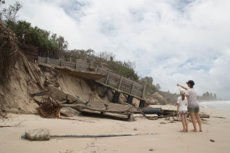 Holidaymakers Kathy Fulton and her eight-year old daughter Beatrice, from Brisbane's Paddington, survey some of the damage at Byron Bay's Main Beach on Tuesday.