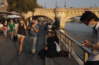 People enjoy the outdoors along the Seine in Paris on Friday.