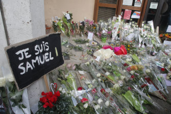 "A placard reading ""I am Samuel"" and flowers lay outside the school where slain history teacher Samuel Paty was working, in Conflans-Sainte-Honorine, north-west of Paris."