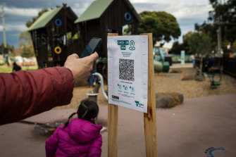 A parent uses a QR code check at a playground in Brunswick when they were reopened in early September.