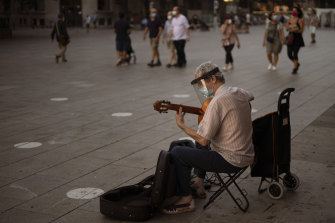 A musician wearing a face mask to prevent the spread of coronavirus plays guitar in downtown Barcelona.