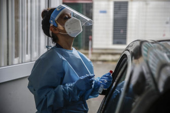 A paramedic works at a COVID-19 drive-through testing site at San Paolo Hospital in Milan.