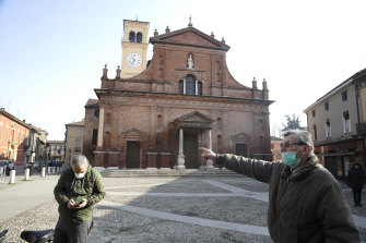People wear masks as they stand in front of the San Biagio church in Codogno, near Lodi, northern Italy.
