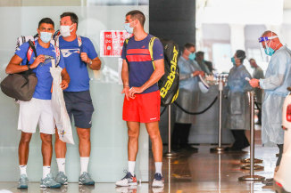 Players wait in front of the Grand Hyatt Melbourne, with staff in full PPE.