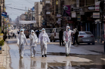 Medical workers oversee the disinfection of streets aiming to halt the spread of the new coronavirus in Qamishli, Syria.