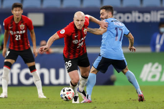 Aaron Mooy pushes past Sydney FC midfielder Anthony Caceres.
