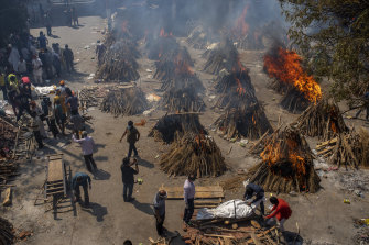 Multiple funeral pyres of victims of COVID-19 burn in an area that has been converted into a crematorium for mass cremation in New Delhi.