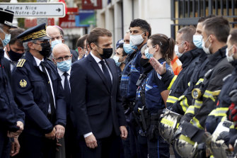 French President Emmanuel Macron meets police and rescue workers outside the cathedral in Nice.