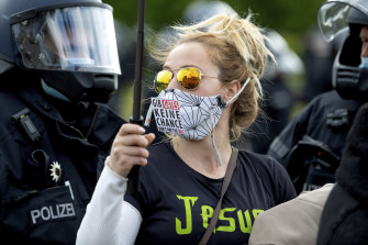 """The Reichstag building, home of the German federal parliament, is mirrored in the glasses of a woman wearing a face mask with the slogan""""Don't Give (Bill) Gates A Chance"""""""
