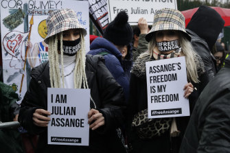 Two supporters wear masks and hold signs during a protest against the extradition of Wikileaks founder Julian Assange outside Belmarsh Magistrates Court in London,
