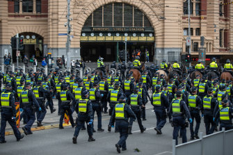 Police officers file past Flinders Street Station on Tuesday afternoon.