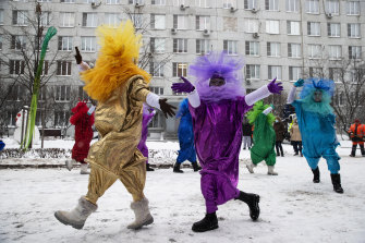 Artists dressed in Christmas costumes perform in the yard of a children's hospital to greet children to mark the upcoming New Year celebrations in Moscow.