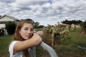 Mia Harris looks on as Defence personnel help clean up her family home in Croki, near Taree, on Monday.