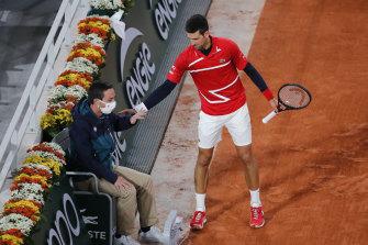 Novak Djokovic checks on the linesman after the ball spun off his racquet and hit the official.