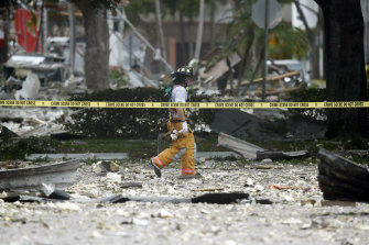 A firefighter walks through the remains of a building after the explosion in Plantation, Florida.