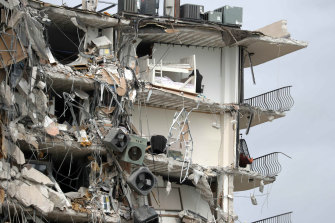 Debris dangles from a section of the collapsed apartment building.