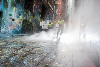 Cleaning in Melbourne's Hosier Lane, where masked people paint-bombed popular street art.