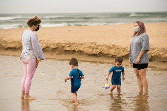 Becc Carroll (right) with a friend and their children at the beach in Torquay.