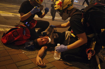 Medical workers help a protester after police fired tear gas in an effort to break up crowds.
