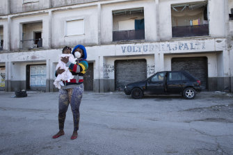 An undocumented worker holds her baby as she walks around the migrant neighbourhood in Castel Volturno, near Naples
