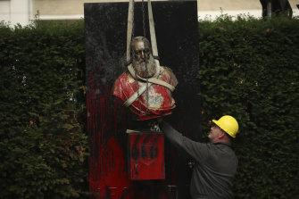 A bust of King Leopold II is hoisted off of its plinth by a crane in a park in Ghent, Belgium, on Tuesday.