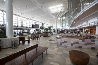 Brisbane Airport's terminals are deserted, but planes filled with freight are still taking off.