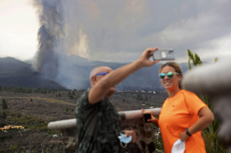 A couple take selfies in front of the volcano eruption on the island of La Palma