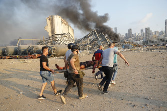 Civilians carry a person at the explosion scene that hit the seaport.
