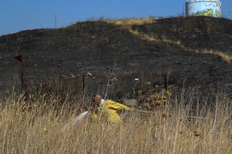 An Israeli firefighter attempts to extinguish a fire caused by rocket near the northern Israeli town of Kiryat Shmona.