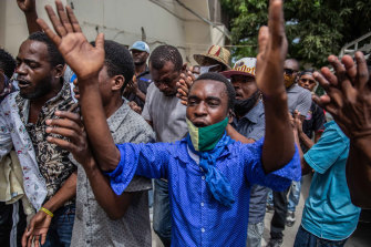 Haitians rally outside a courthouse as prosecutors question senior political figures such as Senate President Youri Latortue and former senator Steven Benoit over the assassination.