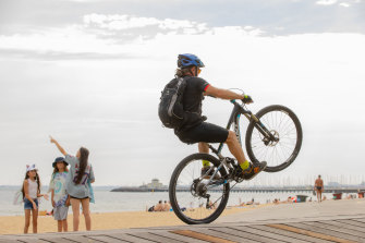 A cyclist pulls a wheelie at St Kilda beach on Thursday.