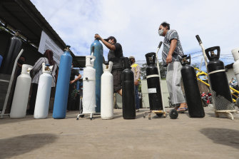 People queue up to refill their oxygen tanks at a filling station in Jakarta