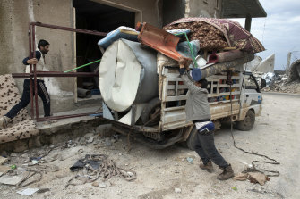 An armed resident loads his truck with belongings during a visit to his home in Balyoun, Syria.