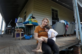 Em Trotter and daughter Evie-Meg, 6, sit on the verandah of their flood-affected home in Croki, near Taree.