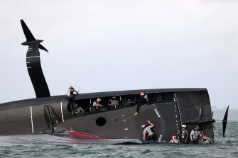 Members of the American Magic team attempt to save their yacht Patriot after it capsized in Auckland on Sunday.