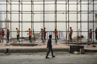 Indian laborers wearing masks report for the day's work at a metro rail construction site in Kochi, Kerala.