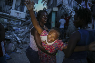 Oxiliene Morency cries out in grief after the body of her 7-year-old-daughter Esther Daniel was recovered from the rubble of their home destroyed by the earthquake in Les Cayes, Haiti.