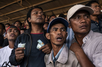 Spectators cheer during a horse race in Bima. Though gambling is illegal in Indonesia, the police are there to stop the occasional scuffles that break out over gambling debts rather than to stop the betting.