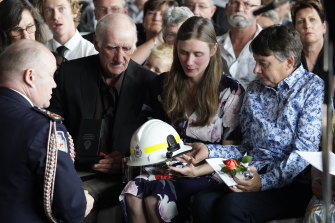 RFS Commissioner Shane Fitzsimmons presents Samuel McPaul's helmet to his widow, Megan, during his funeral.
